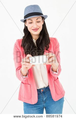 Elegant brunette holding her mobile phone on white background