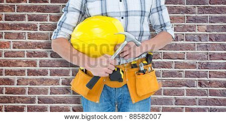 Technician holding hammer and hard hat against red brick wall
