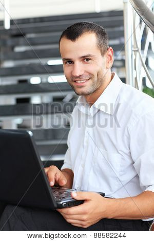 Businessman sitting on stairs and using laptop pc