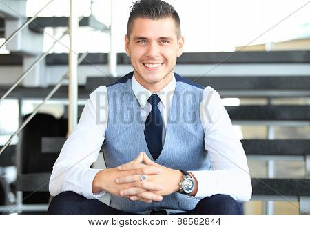 Portrait of positive business man sitting on stairs of modern office