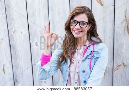 Pretty woman gesturing ok sign against wooden planks
