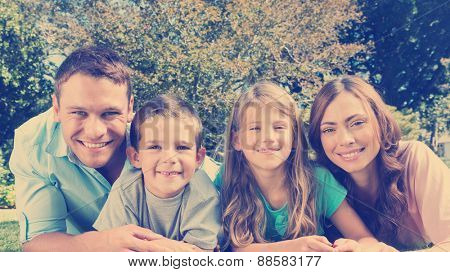 Happy family lying on the grass smiling at camera in park