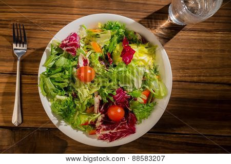 Healthy salad and glass of water on wooden table