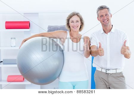 Doctor and patient smiling at camera thumbs up in medical office
