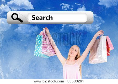 Pretty young blonde holding shopping bags against painted sky