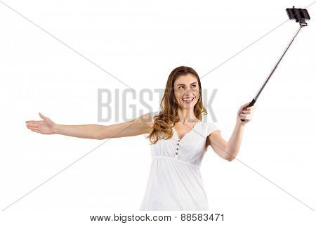 Pretty woman using a selfie stick on white background