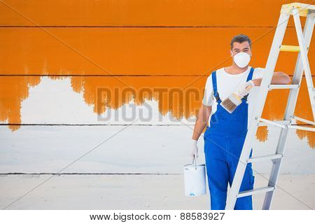 Handyman with paintbrush and can leaning on ladder at home against painted blue wooden planks
