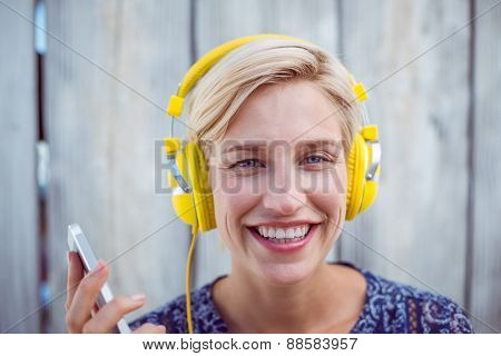 Pretty blonde woman listening music with her mobile phone on wooden background