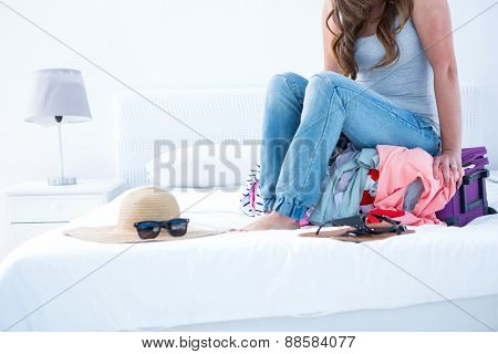 Attractive woman sitting on her case at home in the bedroom