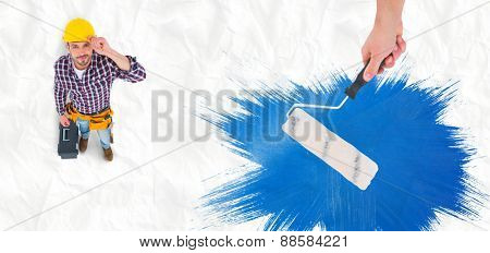 Handyman holding paint roller against crumpled white page