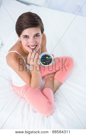 Beautiful woman eating sweet at home in her bedroom