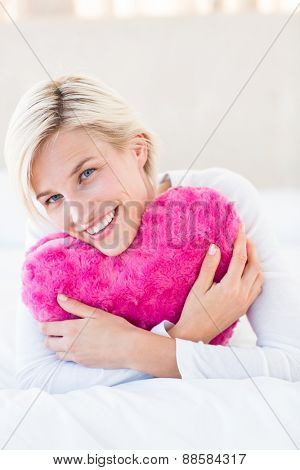 Smiling blonde woman holding heart pillow in the bedroom