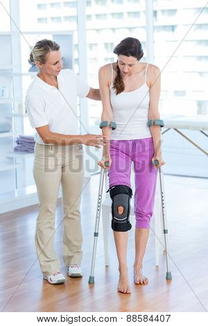 Doctor helping woman walking with crutches in medical office