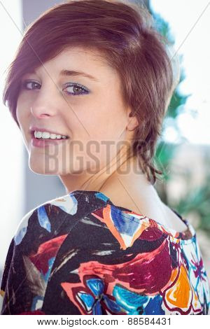 Fit brunette smiling at camera on white background
