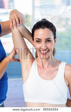 Woman stretching her arm with her therapist in medical office
