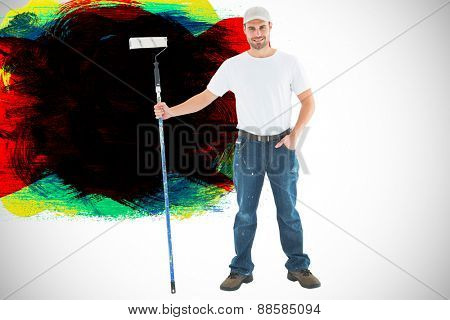 Confident man holding paint roller on white background against red green black yellow and blue paint