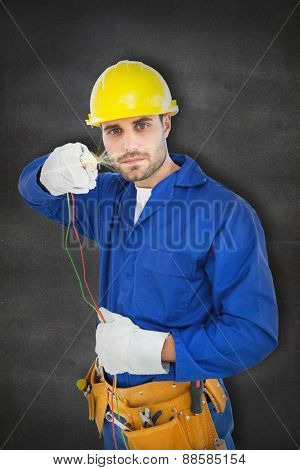 Confident repairman holding cables against black wall