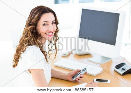 Smiling businesswoman looking at camera on white background