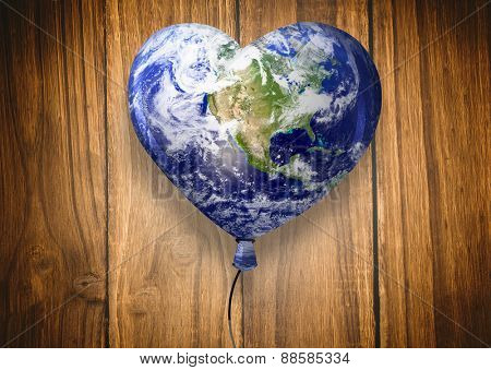 Heart shaped earth against wooden table