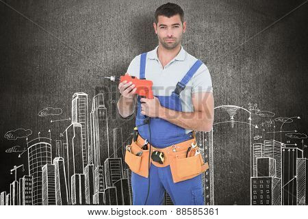Confident male carpenter in overall holding drill machine against hand drawn city plan