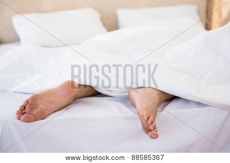 Woman feet under a duvet at home