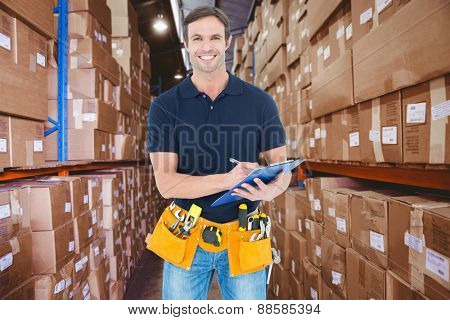 Handsome carpenter writing on clipboard against shelves with boxes in warehouse