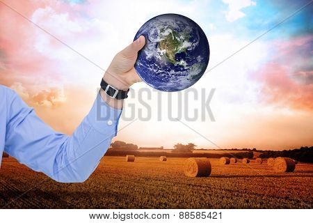 Businessman holding hand out in presentation against countryside scene