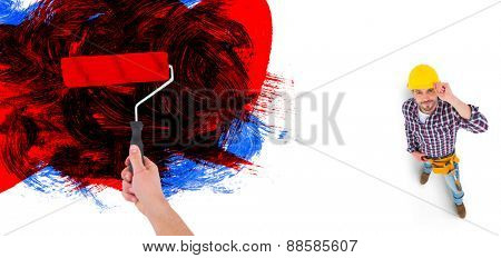 Handyman holding paint roller against black red and blue paint