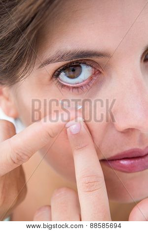Pretty woman applying contact lens on white background