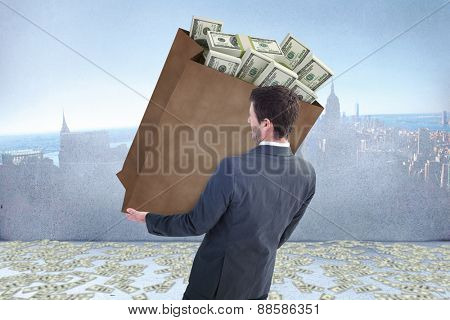 Businessman carrying bag of dollars against city scene in a room