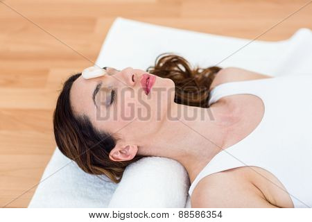 Relaxed brunette lying on mat with stones on wooden floor