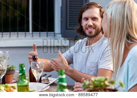 young couple enjoying lunch with white wine outdoors in garden