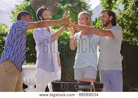 group of friends having outdoor garden barbecue laughing toasting with alcoholic beer drinks