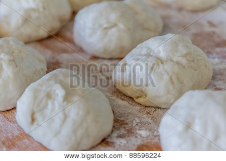 Small balls of fresh homemade dough on floured wooden board