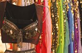 picture of belly-dance  - A Belly Dance Costume Hangs in Front of an Assortment of Colorful Skirts - JPG