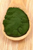 foto of algae  - Closeup of an organic spirulina algae powder and pills in a wooden spoon - JPG