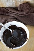 stock photo of chocolate spoon  - chocolate sauce in white bowl with spoon - JPG