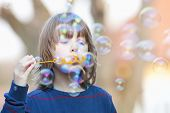 picture of hair blowing  - Boy with Blond Hair Blowing Bubbles Outdoor - JPG