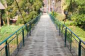 pic of suspension  - blurry defocused image of wooden suspension bridge across the river in rural thailand for background - JPG