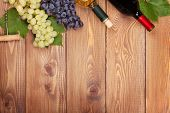 picture of wine grapes  - Red and white wine bottles and bunch of grapes on wooden table with copy space - JPG