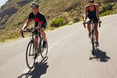picture of triathlon  - Two athletes going down the hill on racing bicycles - JPG