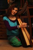 picture of celtic  - Young woman playing celtic harp in a ethno costume