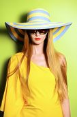 picture of wearing dress  - Beautiful fashionable lady wearing bright yellow dress over green background - JPG