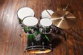 stock photo of drum-set  - Drum set with green color stands on a brown background - JPG