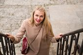 picture of exaltation  - Young woman in coat smiles and walks up the stairs - JPG