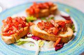 pic of antipasto  - Fresh homemade crispy Italian antipasto bruschetta topped with tomato - JPG