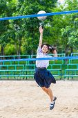foto of schoolgirls  - Cute Thai schoolgirl is playing beach volleyball in school uniform. Focus on the model face.
