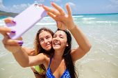 stock photo of two women taking cell phone  - two happy sexy girls selfie smartphone on beach - JPG