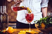 stock photo of sangria  - Man pours homemade sangria with fruit pieces in a glass. Refreshing summer drinks