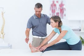 foto of physiotherapist  - Physiotherapist helping his patient stretching in medical office - JPG